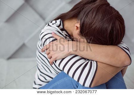 Serious Problems. Depressed Cheerless Unhappy Woman Sitting On The Floor And Crying While Having Ser