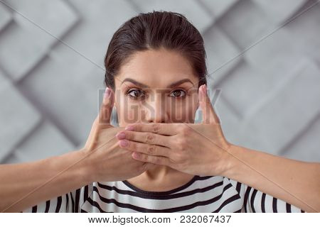 Social Problem. Sad Cheerless Young Woman Looking At You And Covering Her Mouth While Being Silent A