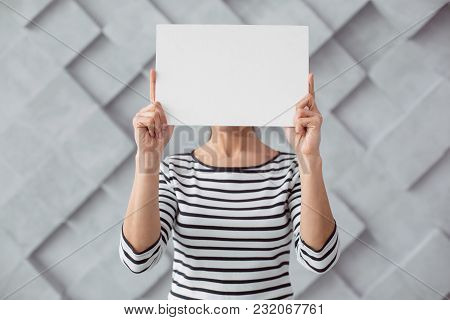Read This. Nice Pleasant Young Woman Standing And Covering Her Face While Holding A Sheet Of Paper