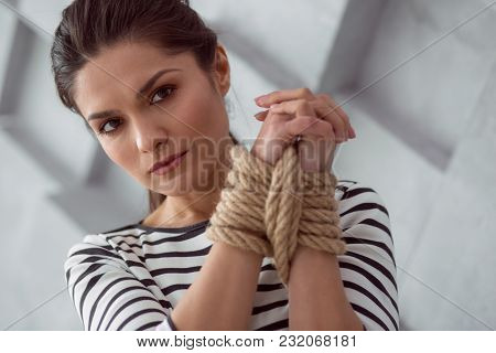 Female Victim. Sad Moody Cheerless Woman Holding Her Hands Together And Looking At You While Being T