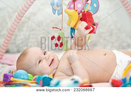Baby Lying On Developing Rug. Playing In Mobile. Educational Toys. Sweet Child Crawling And Playing