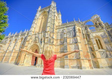 Tourism In Portugal. Freedom Lifestyle Female Tourist At Batalha Monastery. Caucasian Woman Enjoying