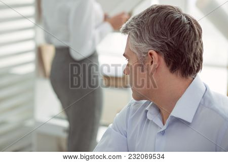 Very Interesting. Nice Pleasant Adult Man Sitting At The Table And Turning His Head While Looking At