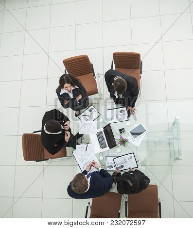 Top View Of Business Team On Meeting Discussing Financial Charts Profits Of The Company In A Modern