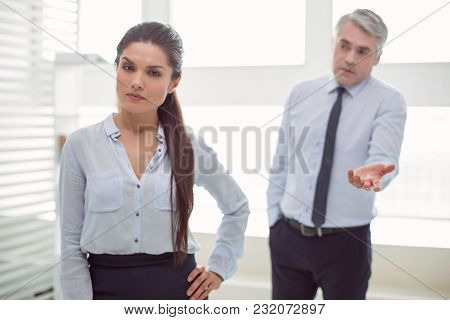 Complicated Relationships. Serious Unhappy Attractive Woman Standing In The Office And Listening To