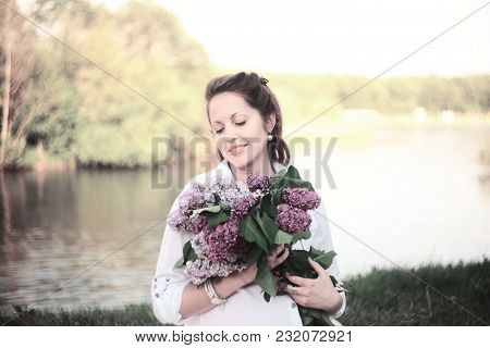 Pregnant Young Woman With A Bouquet Of Lilacs In The Park On A Sunny Day