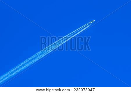 Airplane With A Condensation Track On A Blue Sky Moving Diagonally Upwards