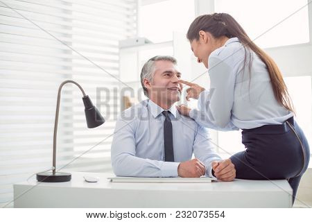 Relationships At Work. Nice Positive Attractive Woman Looking At Her Boss And Flirting With Him Whil