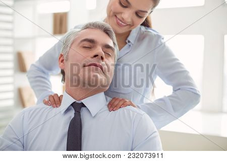 Absolutely Relaxed. Pleasant Nice Adult Man Sitting In The Chair And Closing His Eyes While Receivin