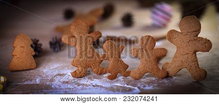 Candles And Gingerbread Men At The Christmas Table .photo With Copy Space.