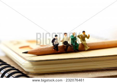 Miniature People: Business Team Sitting On  Pencil And Book. Concept Of Education And Business.