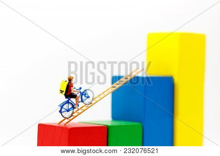 Miniature People: Traveler Riding Bicycle On Wood Ladder With Growth Graph, Concept Of The Path To P