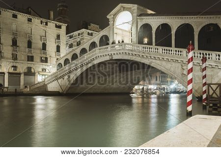 Famous Rialto Bridge Illuminated By Night Above Waters Of Grand Canal