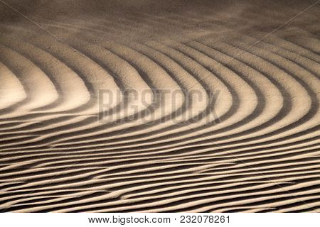 Sand blowing over sand dunes in wind, Sahara desert