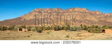 Moroccan clay houses near orange mountains in palm tree oasis, Morocco, North Africa, panorama
