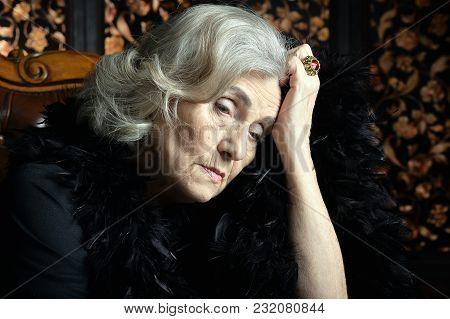 Portrait Of Sad Senior Woman In Boa  Posing At Home