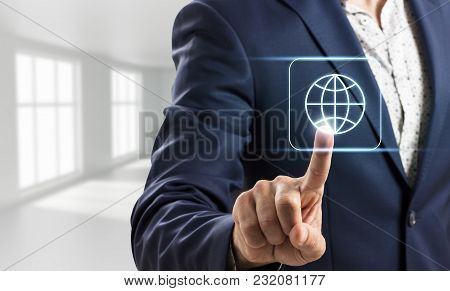 Businessman Touches Virtual Global Icon In Bright White Office.