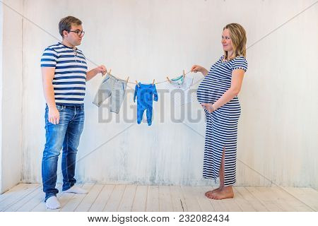 Young Couple: Pregnant Woman And Man Holding Baby Clothes