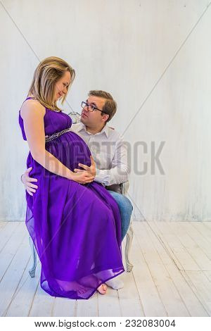 Beautiful Couple: Pregnant Woman And Man Sitting Near Brick Wall