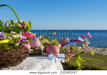 Colorful Easter Eggs And Branch With Flowers By The Sea