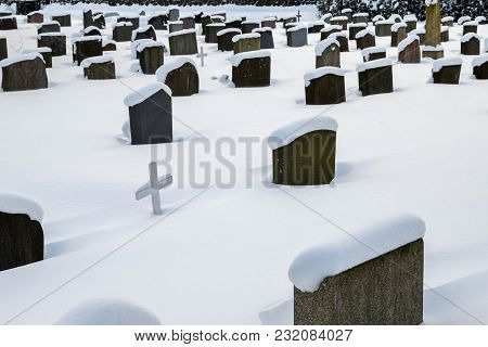 Grave Stones In The Snow, With A White Wooden Cross In Between