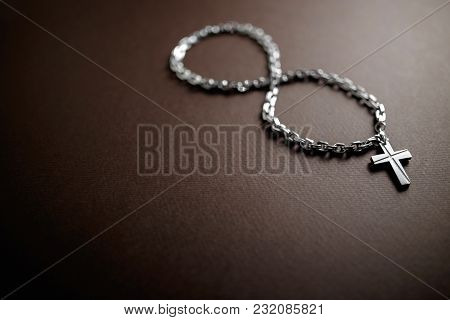 Silver Christian Cross And Chain On Brown Background With Infinite Symbol
