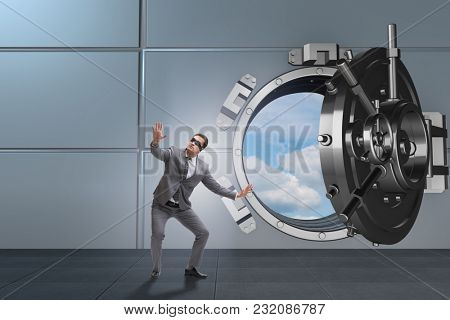 Blindfolded businessman in front ot vault door