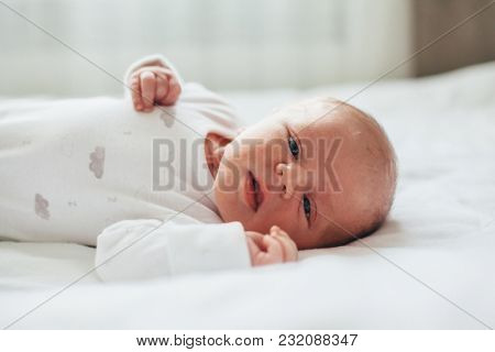 Portrait of a newborn baby lying on a bed in a bright room.