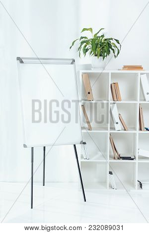 Empty Flipchart And Wooden Shelves With Folders In Office