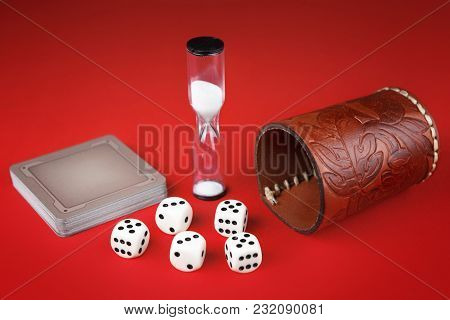 Dice, Cards And Leather Cup On Red Background