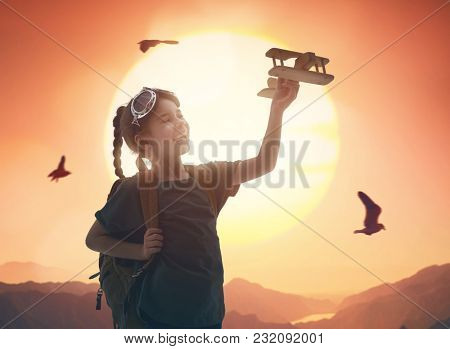 Dreams of flight! Child kid girl playing with toy airplane against the sky at sunset.