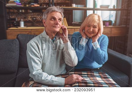 Old But Beautiful People Are Listening To Music Through The Headphones. They Are Sharing One Pair Of