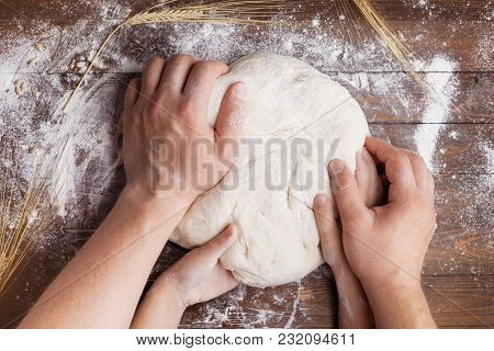 Father And Child Hands Prepares The Dough With Flour On Wooden Table From Above. Homemade Pastry For