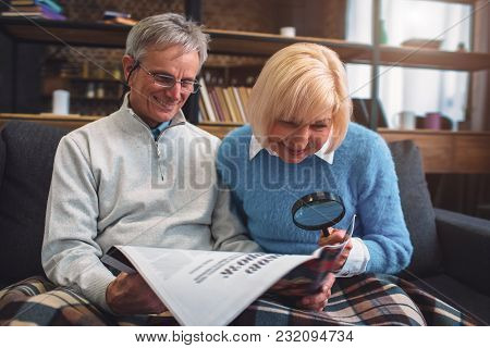 Interesting Picture Of White-haired Man And Woman Sitting On The Couch And Reading A Newspaper. Man