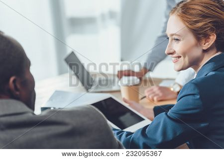Woman With Difital Tablet In Hands Smiling To Sitting African Man