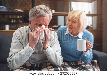 This Ill Man Is Sneezing Into The Napkin. His Wife Is Sitting Besides Him And Advising To Drink Hot