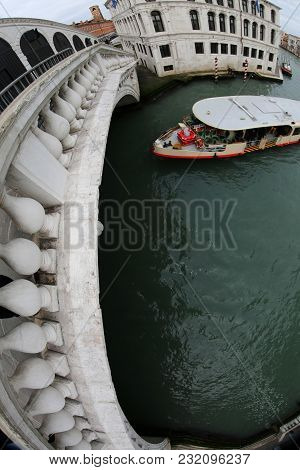 Rialto Bridge With Fisheye Lens And A Ferry Boat In Venice Italy