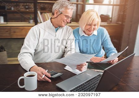 Nice Picture Of Senior Man And Woman Studying Papers At The Table. The Are Doing That Together With