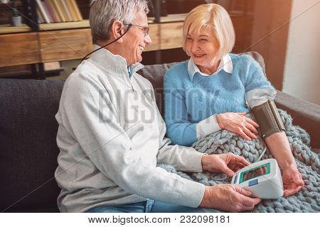 A Picutre Of Happy Old Couple That Like To Be Together. The Woman Is Measuring Her Blood Pressure. T