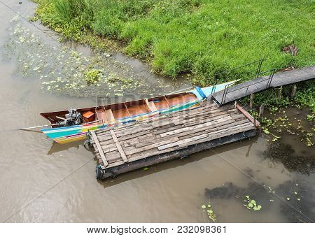 Long Tail Boat Near The Small Wooden Pontoon For Service The Traveler In The Countryside Of Thailand