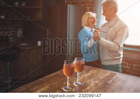 Nice And Warm Picture Of Old Ouple Dancing Together In The Kitchen. They Have Left Two Full Wineglas