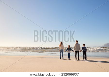Rear View Of Family On Winter Beach Holding Hands Looking At Sea