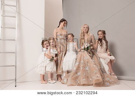 The Two Brides And Little Pretty Girls With Flowers Dressed In Wedding Dresses. Lovely Little Girlfr
