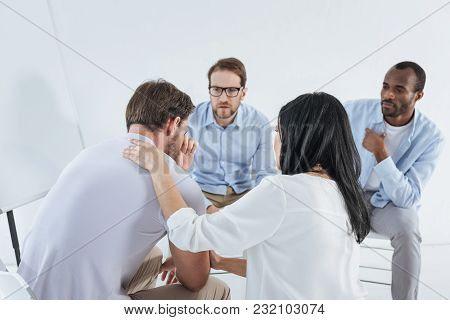 Multiethnic Mid Adult People Sitting On Chairs And Supporting Upset Man During Anonymous Group Thera