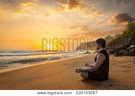 Young sporty fit man doing yoga meditating in padmasana lotus pose on tropical beach on sunset