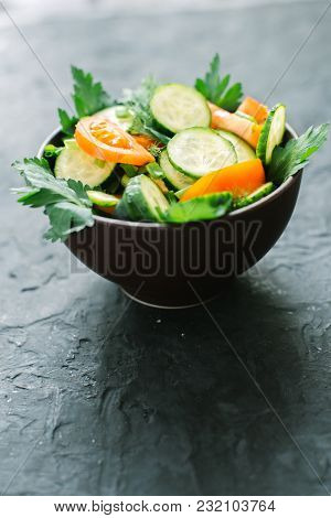 Fresh Salad With Vegetables On A Black Matte Background. The Concept Of A Healthy Diet.