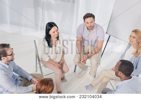 High Angle View Of Smiling Multiethnic Middle Aged People Sitting On Chairs And Talking During Group