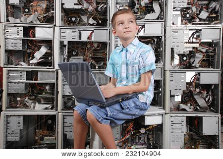 The Boy Works Behind A Portable Computer On A Background Of A Wall From Old Computers. Horizontal Or