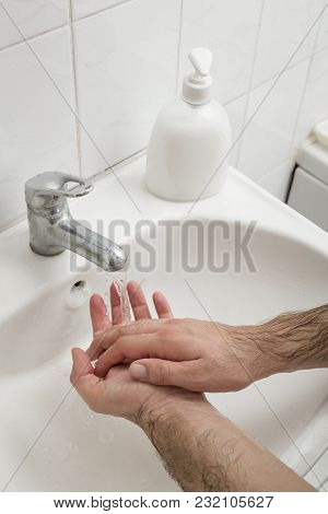 Close Up Of A Man Washing Hands On The Bathroom Sink. Selective Focus On The Hand
