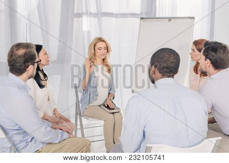 Middle Aged Woman Holding Hand On Holy Bible While Sitting With Multiethnic People On Chairs At Grou